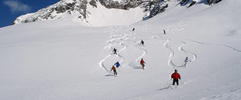Skiers ski off piste down a mountain in Europe on a sunny day