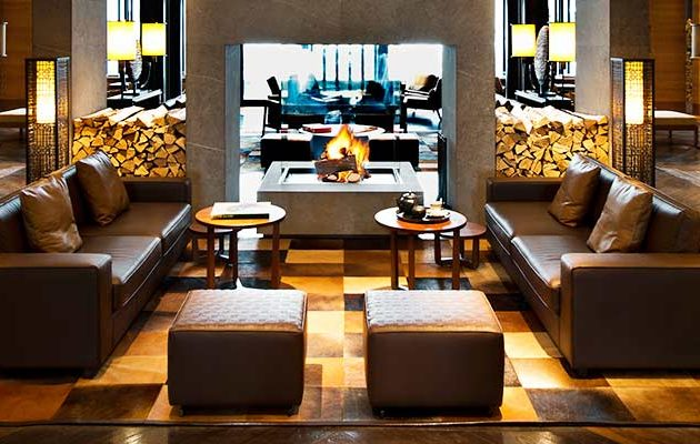 A luxurious seating area in The Chedi Andermatt hotel in front of a fire