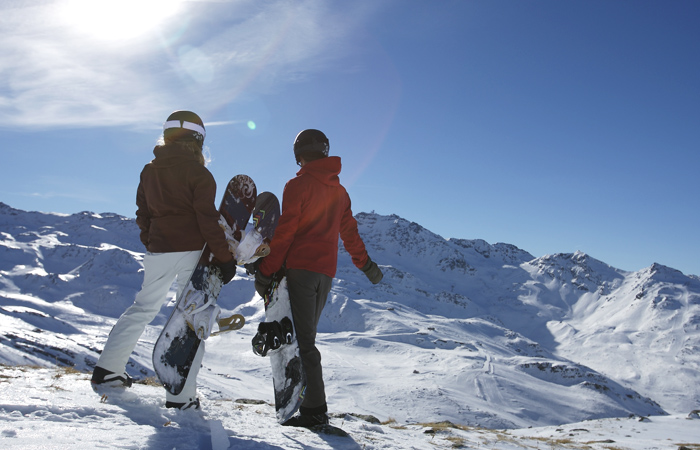 Snowboarders standing on piste